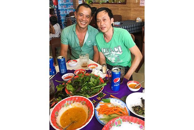 Nghệ sĩ Hoài Linh (bên phải) thưởng thức nem Ninh Hòa tại quán nem Bà Năm. (Ảnh do chủ quán cung cấp).